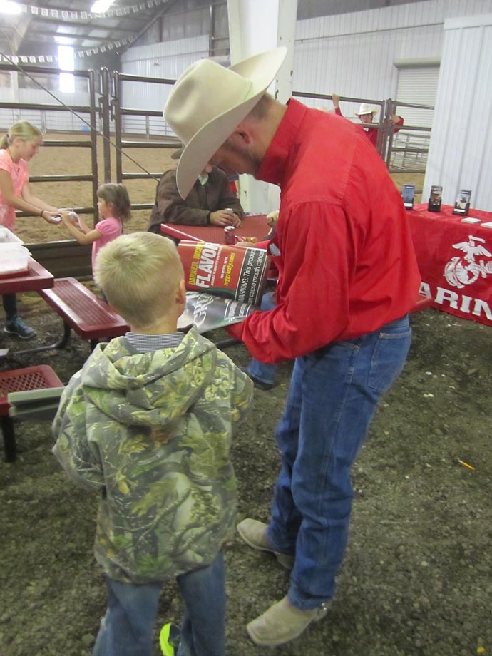 A father flips through an issue of Sports Illustrated with a young rodeo fan.