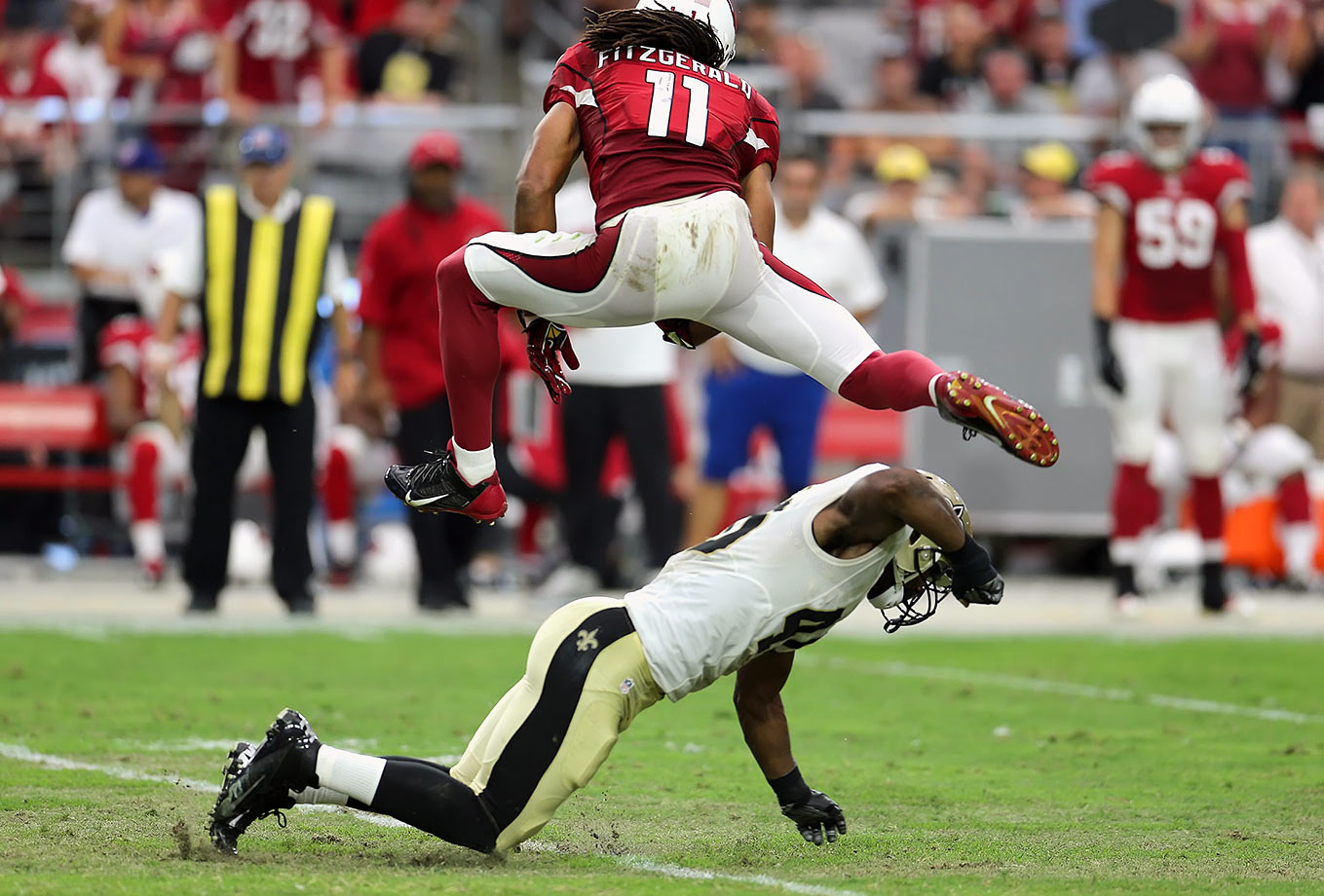 Wide receiver Larry Fitzgerald leaps over defensive back Delvin Breaux of the New Orleans Saints during the Arizona Cardinals victory.