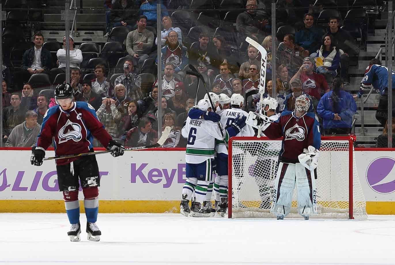 One of those nights: Avalanche netminder Semyon Varlamov and winger Gabriel Landeskog have that hangdog look—as do their fans at Denver's Pepsi Center—while the Canucks celebrate yet another tally on the way to their 5-2 rout on November 4, 2014.
