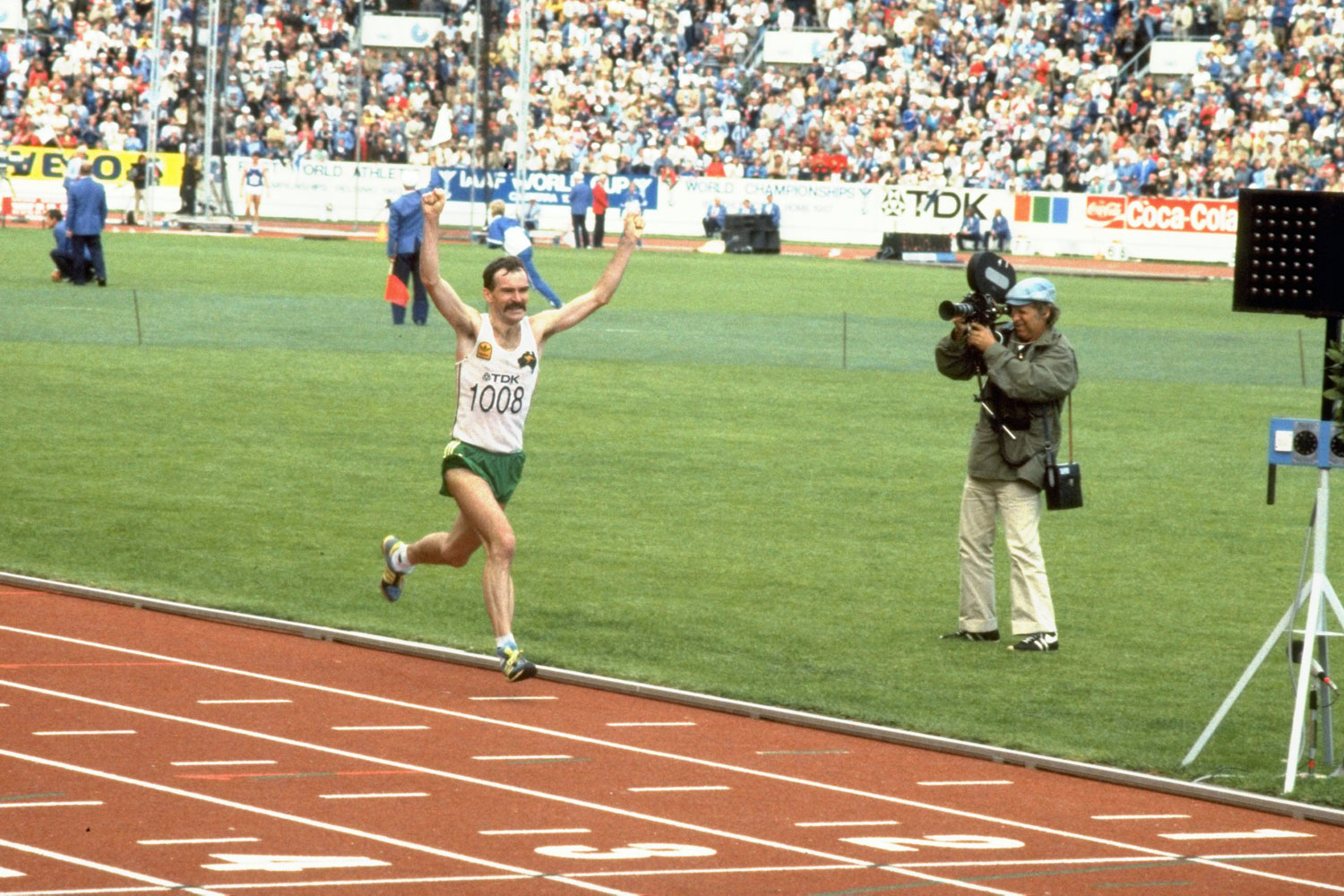 Rob de Castella celebrates as he crosses the finish line to win the marathon event during the World Championships at the Olympic Stadium in Helsinki, Finland.