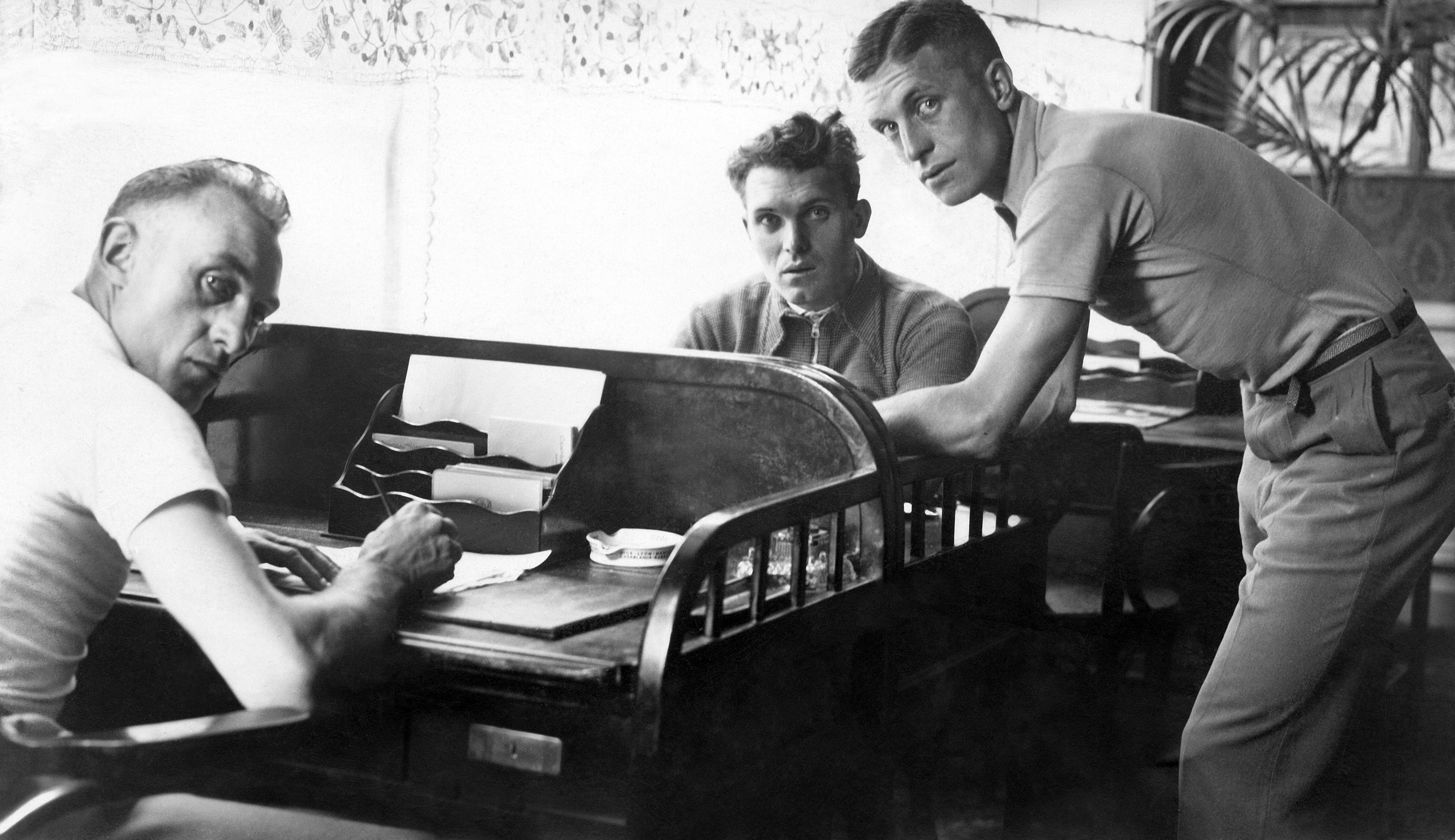 Belgian team racing cyclists Georges Ronsse (left), Frans Bonduel (center) and Jean Aerts (right) write letters during a rest time of the Tour de France, on July 8, 1932 in Nantes.