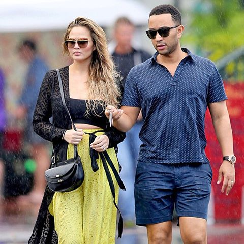 Oh the weather outside is frightful, but that won't stop John Legend and Chrissy Teigen from celebrating their babymoon in Hawaii. umbrella (AKM-GSI)