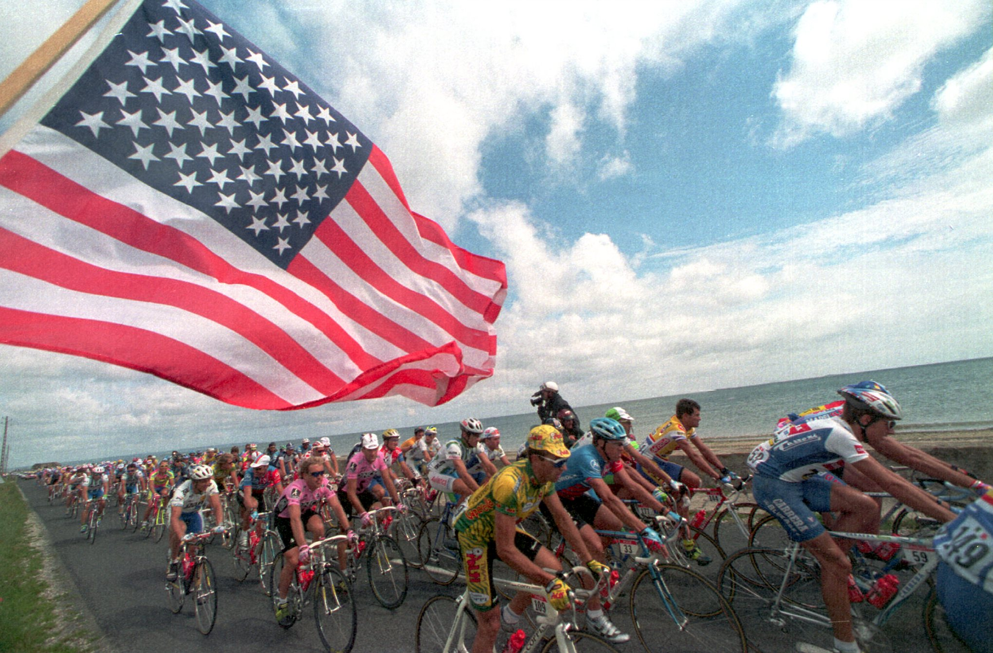 The American flag flutters in the air in the foreground as the pack of riders pass under it on their way up the coast during stage six of the Tour de France in 1994.
