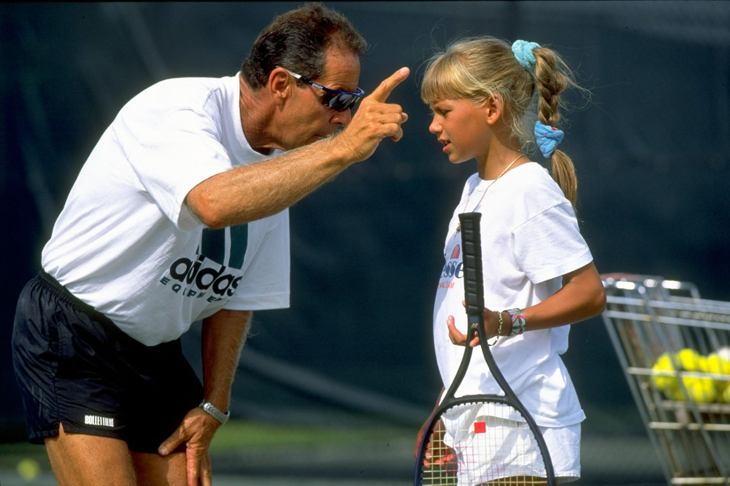 Tennis coach Nick Bollettieri gives instructions to a young Anna Kournikova during a training session at his Tennis Academy in Bradenton, Florida.