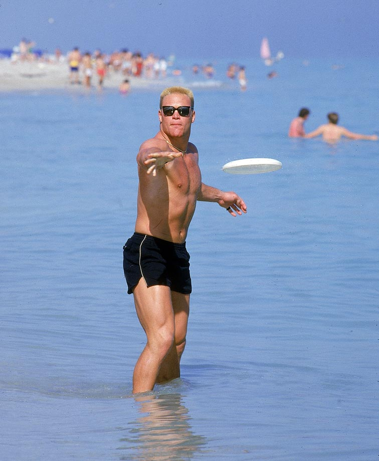 "In advance of the 1986 Orange Bowl, Oklahoma's Brian ""The Boz"" Bosworth throws a Frisbee on a sunny Florida beach. At the following year's Orange Bowl, he would famously wear a ""National Communists Against Athletes"" T-shirt on the sidelines in response to being suspended by the NCAA for steroid use."