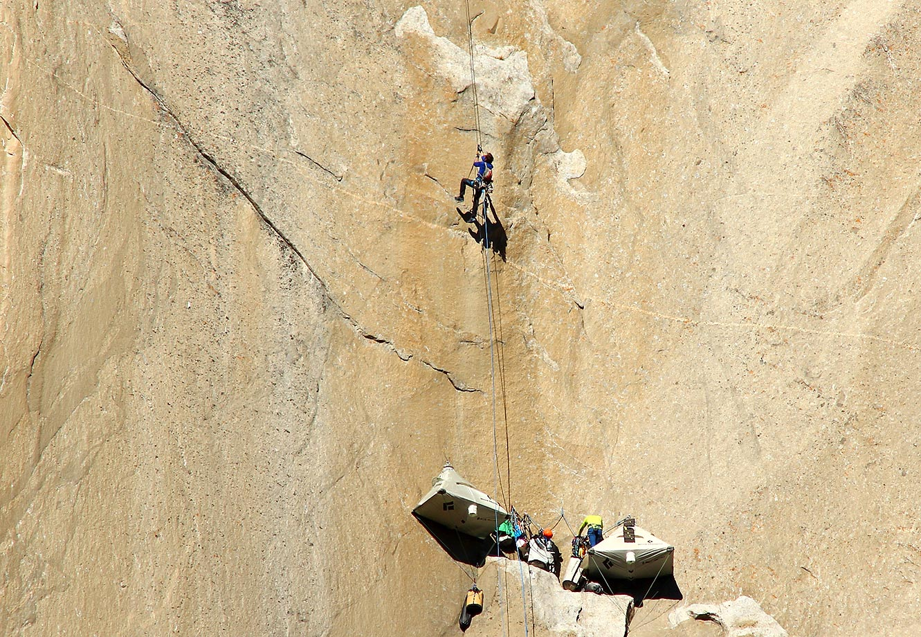 Kevin Jorgeson (in blue) ascending the rope from base camp to his next climb, while Tommy Caldwell sorts gear at camp (in yellow.)