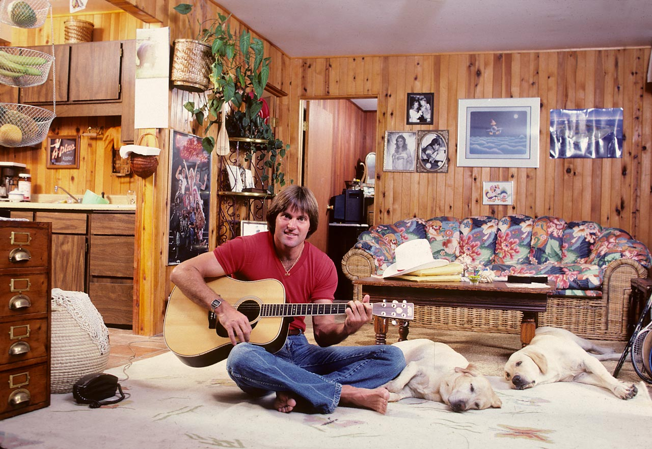 Before becoming a staple of U.S. reality television series, Bruce Jenner was an American Olympic hero and, believe it or not, a smash hit with females all over the country. Here, at 31 years old, he strums on an acoustic guitar in his Malibu home, much to the dismay of his two yellow labs.