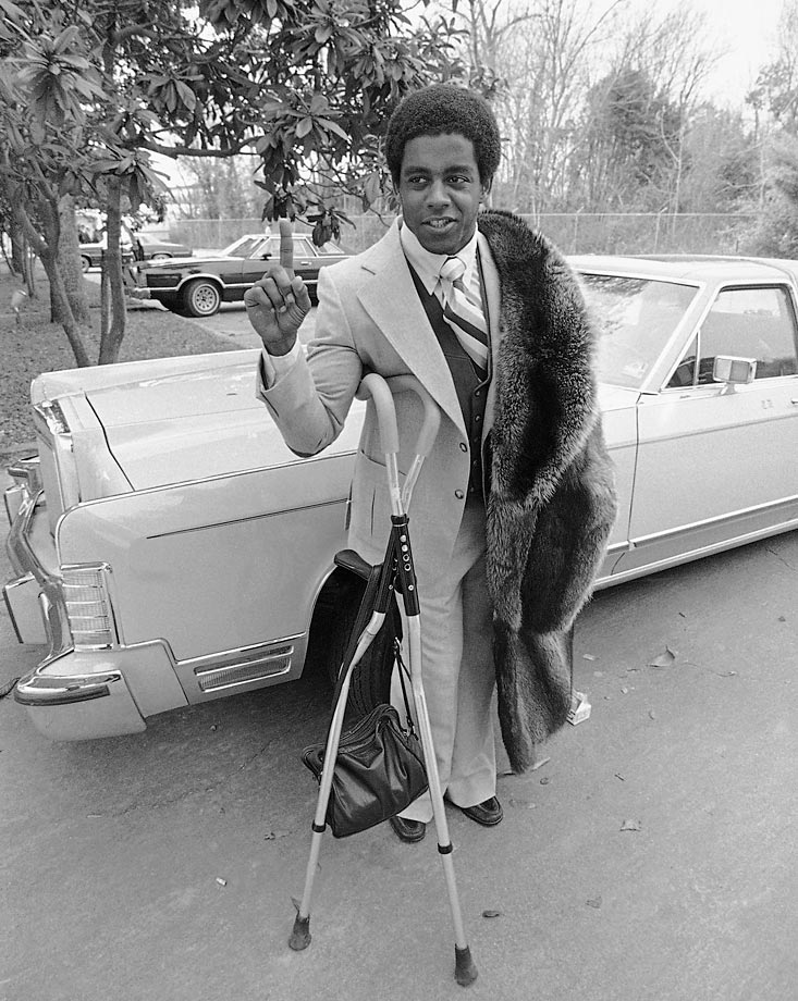 Tony Dorsett standing beside his car, holding up a number one sign, and resting against his crutches. Dorsett was a four time Pro Bowl pick.