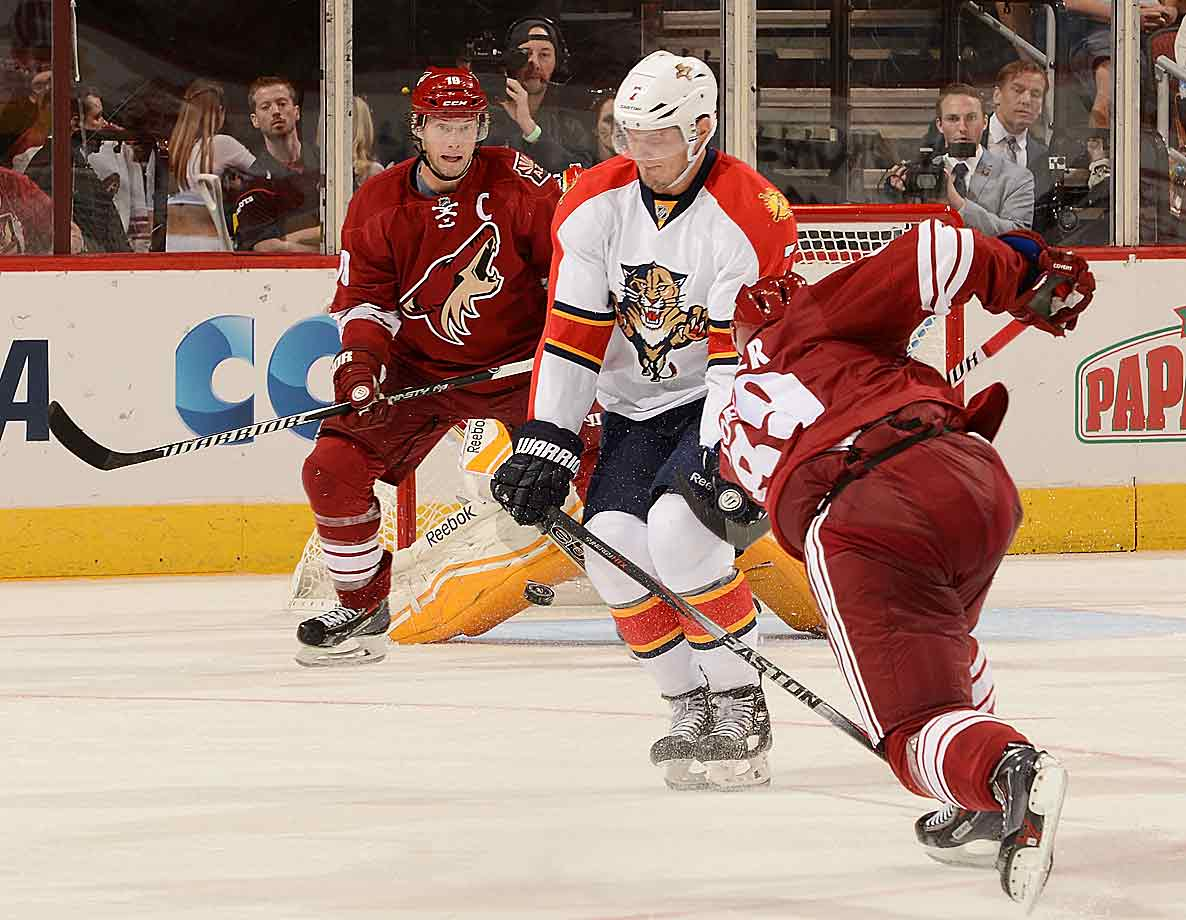 In the line of fire: Panthers defenseman Dylan Olsen and Coyotes forward Shane Doan prepare to pay the cold, hard price as winger Mikkel Boedker (foreground) unleashes a shot during a game at Gila River Arena on Oct. 25, 2014.