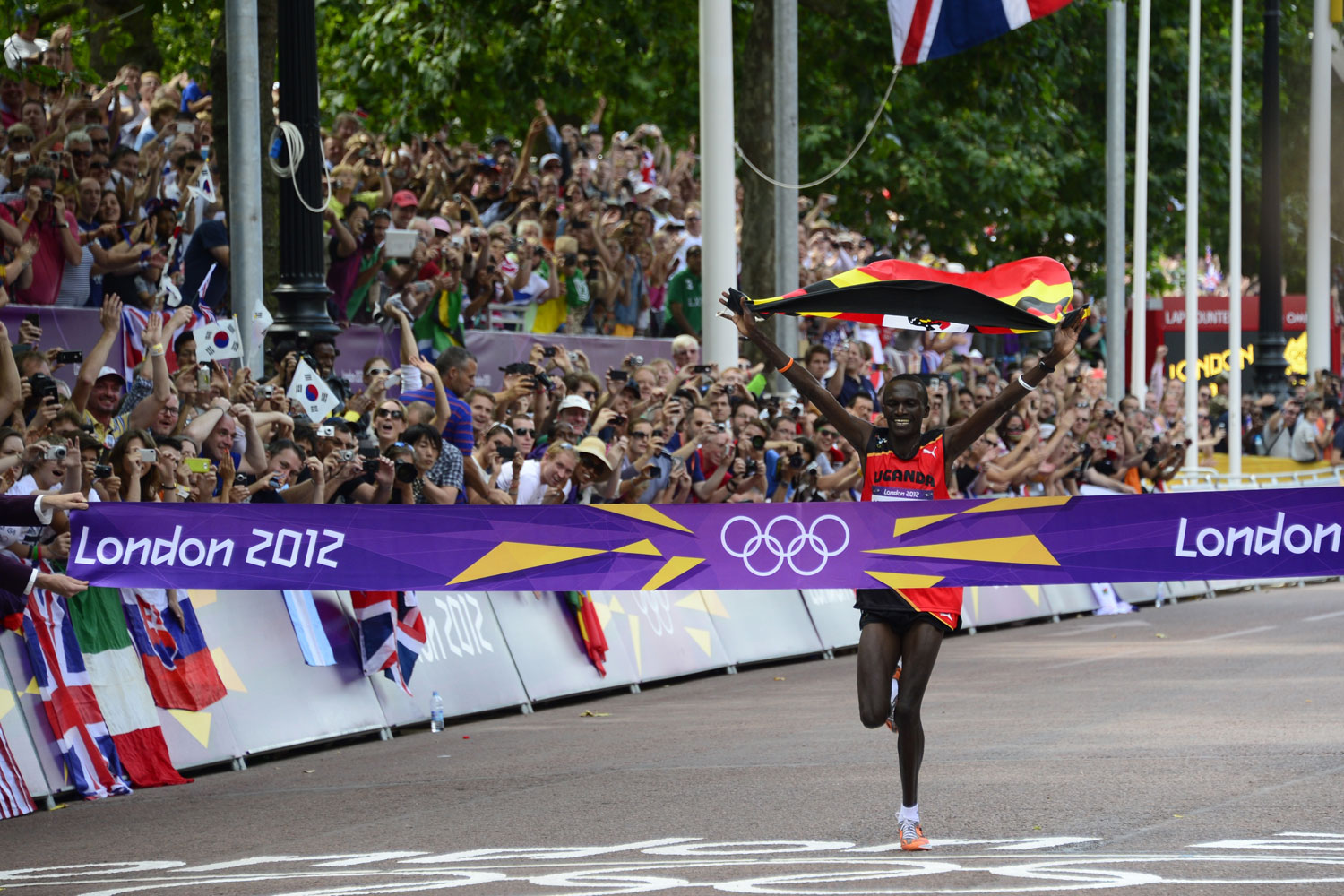 Uganda's Stephen Kiprotich waves his national flag as he crosses the finish line to win the athletics event men's marathon during the London 2012 Olympic Games on August 12, 2012 in London.