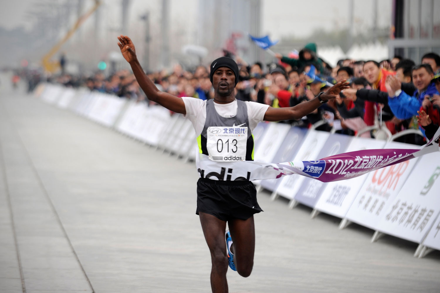 Ethiopia's Tariku Jufar Robi crosses the finish line to win the men's portion of the Beijing Marathon in November 2012. A total of 30,000 runners took part in the race.