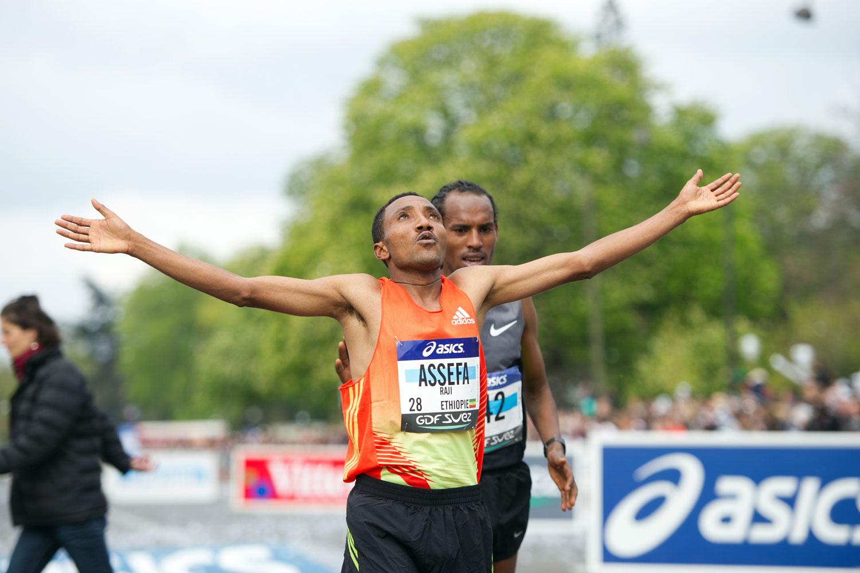 Raji Assefa (L) crosses the finish line ahead of Sisay Jisa (R) during the 36th Paris Marathon in April 2012.