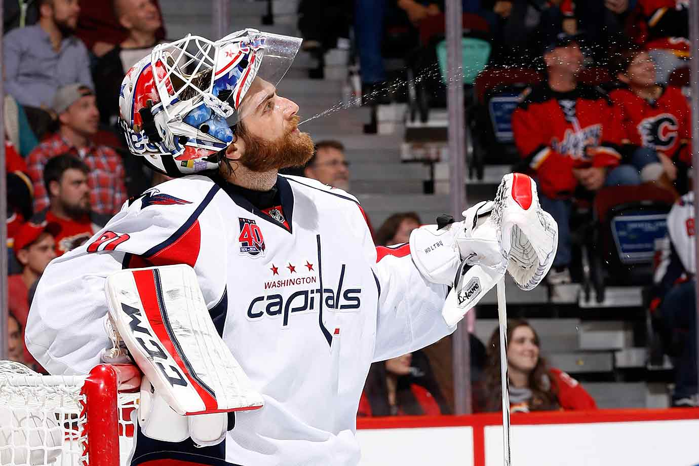 The spitting image. The Capitals' goaltender tries to douse the Flames during a game at Calgary's  Scotiabank Saddledome on Oct. 25, 2014.