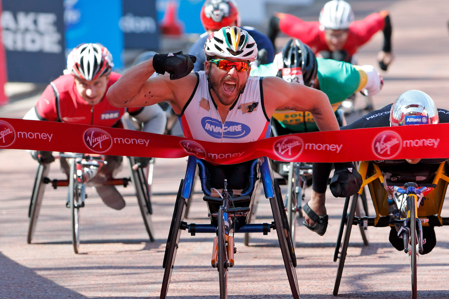 Kurt Fearnley pumps his fist as he crosses the finish line to win the men's wheelchair race at the Virgin London Marathon 2013.