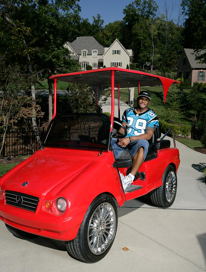 Carolina Panthers wide receiver Steve Smith smiles in this interesting red vehicle.