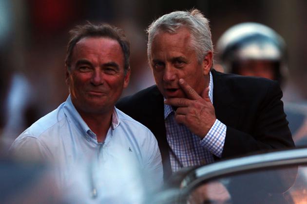 Former Tour winner Bernard Hinault (L) and Greg LeMond share a joke after the twenty first and final stage of the 2013 Tour de France.
