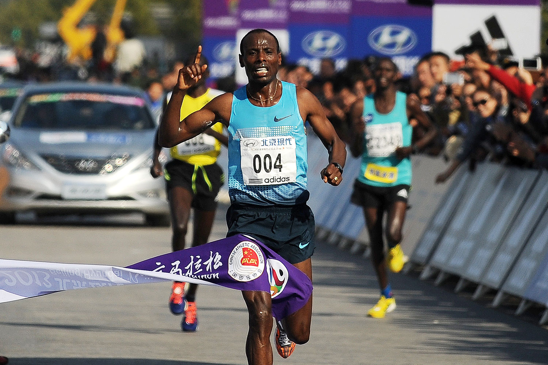Ethiopia's Tadese Tola Woldegeberel (C) crosses the finish line to win the Beijing Marathon in October 2013.