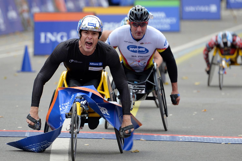 Marcel Hug crosses the finish line to win the Men's Wheelchair Division of the New York City Marathon on November 3, 2013.
