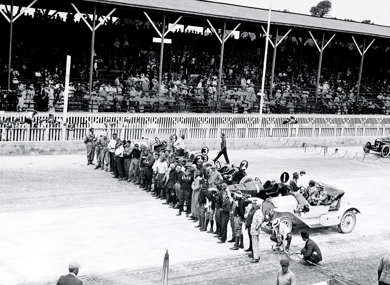 The lineup for Indy's first 500-mile race was led by a convertible pace car (lower right). The photographer? Yes—it's Mr. Henry Ford.