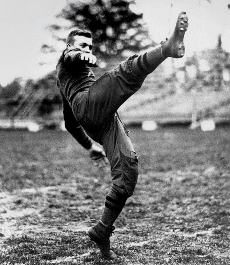 A young Dwight Eisenhower kicks a football during a practice session at West Point in 1912.