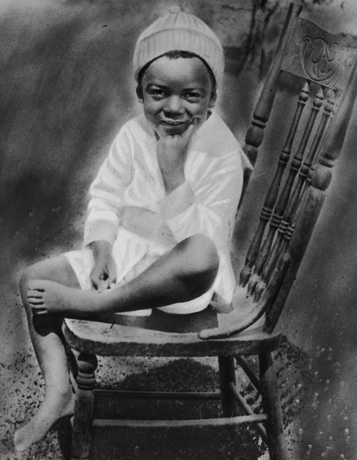 Jackie Robinson, as a young boy, poses while sitting on a chair, circa 1925.