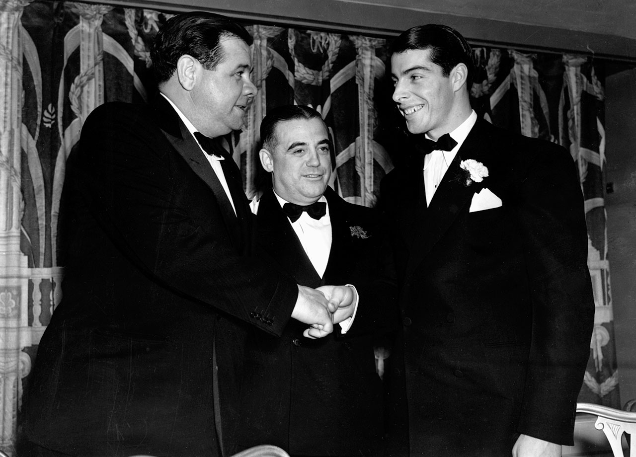 Babe Ruth and Joe DiMaggio shake hands as they meet for the first time on Jan. 24, 1938 at a sports banquet in New York City.  New York sports writer Bill Corum (center), introduced former Yankee the Babe to the 1937 home run champion, DiMaggio.