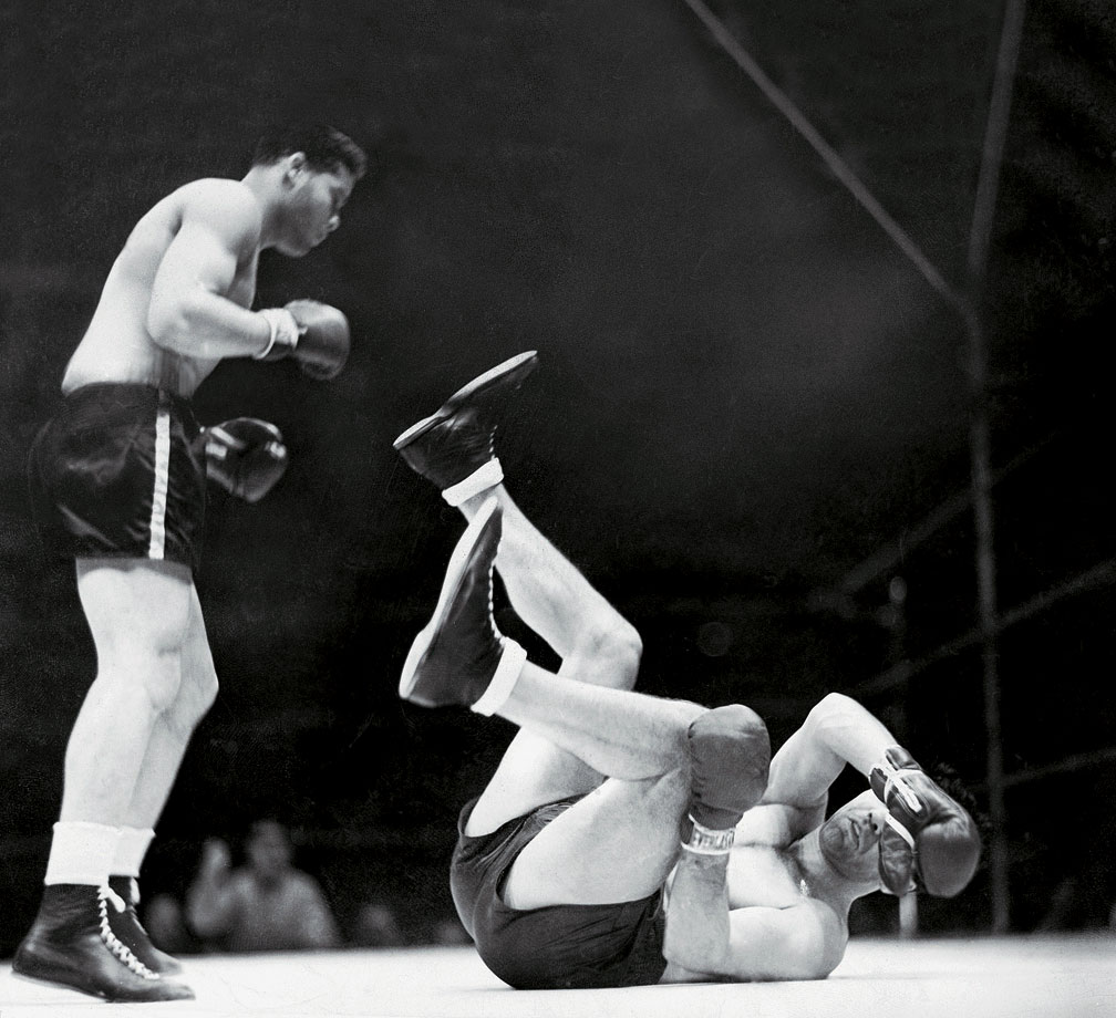"The new heavyweight king had unfinished business. ""I don't want to be called champ,"" Louis said, ""until I whip Max Schmeling."" Louis would get his chance in a match that took on international significance far beyond boxing. With Hitler in power and a second world war looming, Louis was cast as the defender of democracy against Schmeling, the hero of Nazi Germany. Louis trained with determination for the bout and when he entered the ring in Yankee Stadium, he was at his peak. He unleashed a frighteningly effective attack on Schmeling, dropping him three times before referee Arthur Donovan stopped the fight just 2:08 into the first round. Wrote poet Maya Angelou of black America's reaction to Louis' victory, ""Champion of the world. A Black boy. """