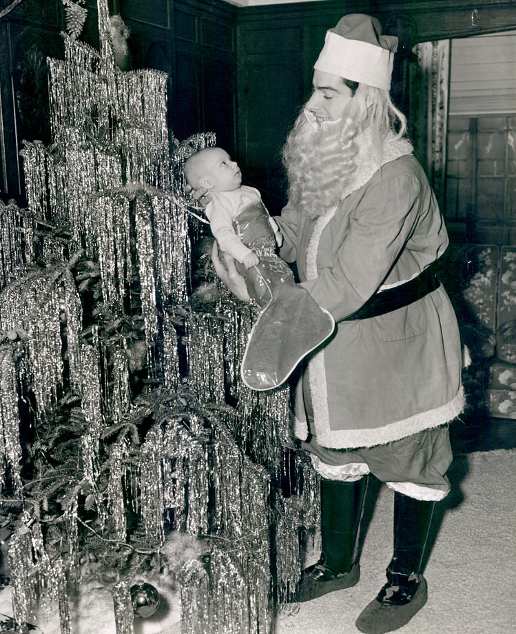 Joe DiMaggio plays Santa Claus with his newborn son, Joe DiMaggio III, in Dec. 1941.