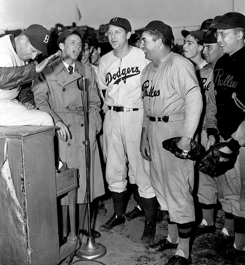 Frank Sinatra sings at the Red Cross War Fund baseball game between the Brooklyn Dodgers and Philadelphia Phillies at Ebbets Field on April 13, 1944. He is joined in harmony by Dodgers coach Charley Dresser (left), Dodgers outfielder Dixie Walker (center) and Phillies manager Freddie Fitzsimmons (right center).