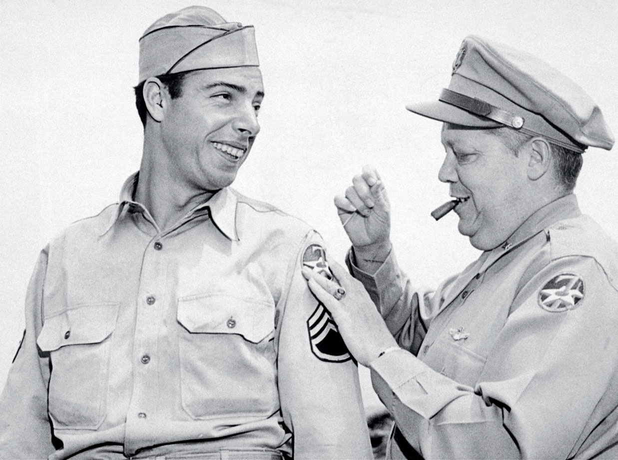 Sergeant Joe DiMaggio gets some help from Brigadier General William J. Flood, sponsor of the 7th Army Air Force overall sports program, in sewing on his shoulder patch on June 9, 1944.