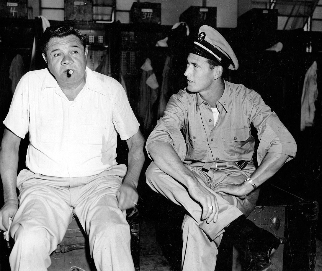 Babe Ruth sits with Ted Williams, sitting in his Navy uniform, circa 1945.