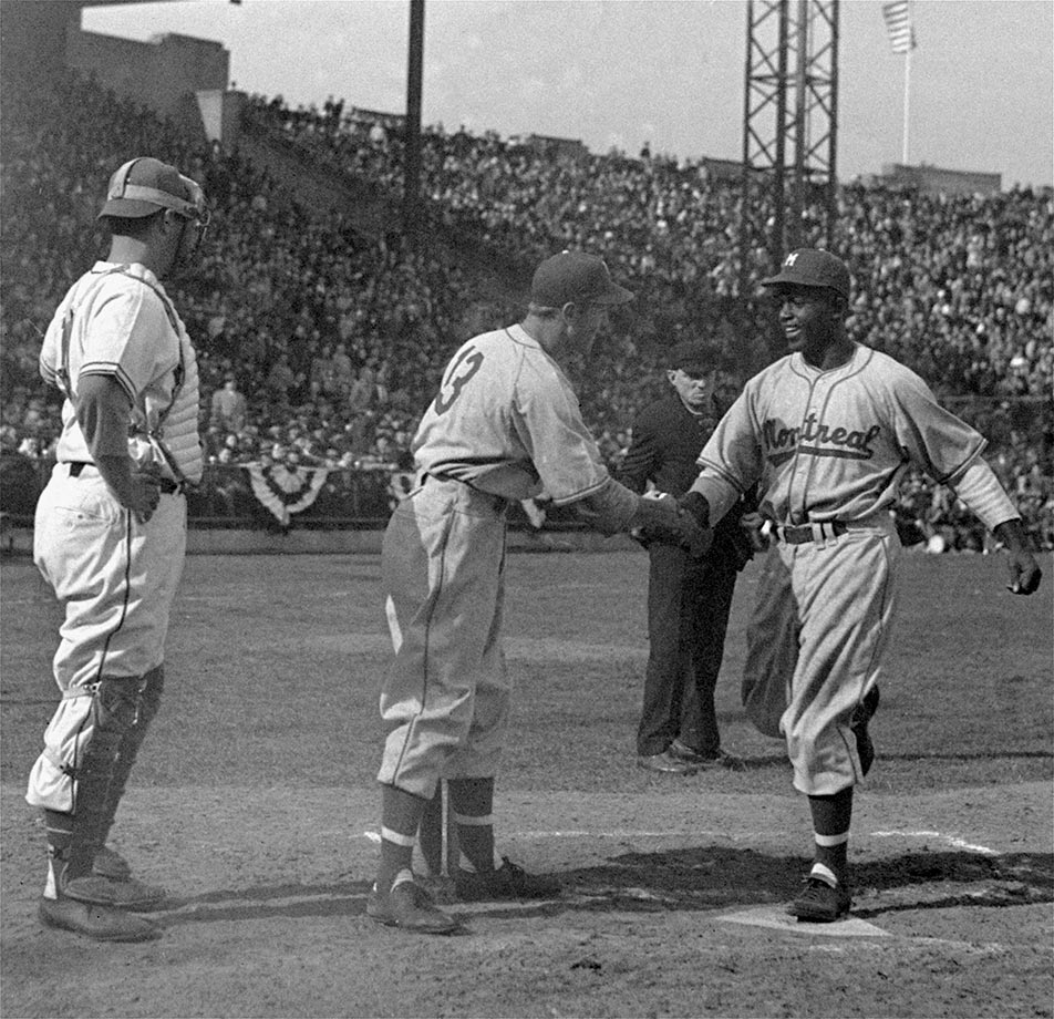 Montreal outfielder George Shuba congratulates teammate Jackie Robinson as he crosses the plate after hitting a home run in the third inning against the Jersey City Giants at Roosevelt Stadium in Jersey City, N.J., during his professional debut on April 18, 1946.