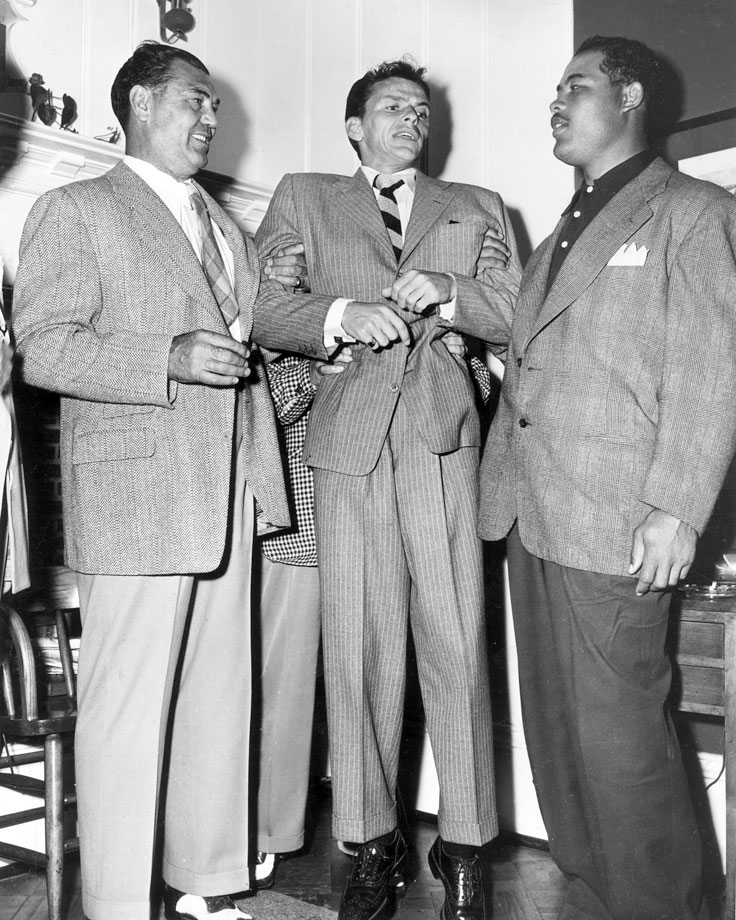 Jack Dempsey (left) and Joe Louis lift up Frank Sinatra by his arms, circa 1947.