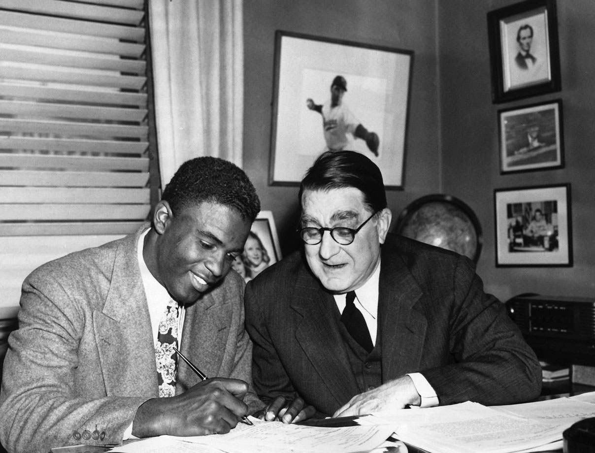 The architect of the Brooklyn Dodgers dynasty, Branch Rickey, has Jackie Robinson sign another contract before the 1948 season.