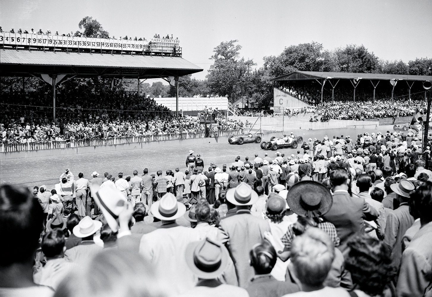 Crowds came out in full force (as well as in full headgear) and saw Mauri Rose win his third, and last, 500. Rose's car is far left at the starting line.