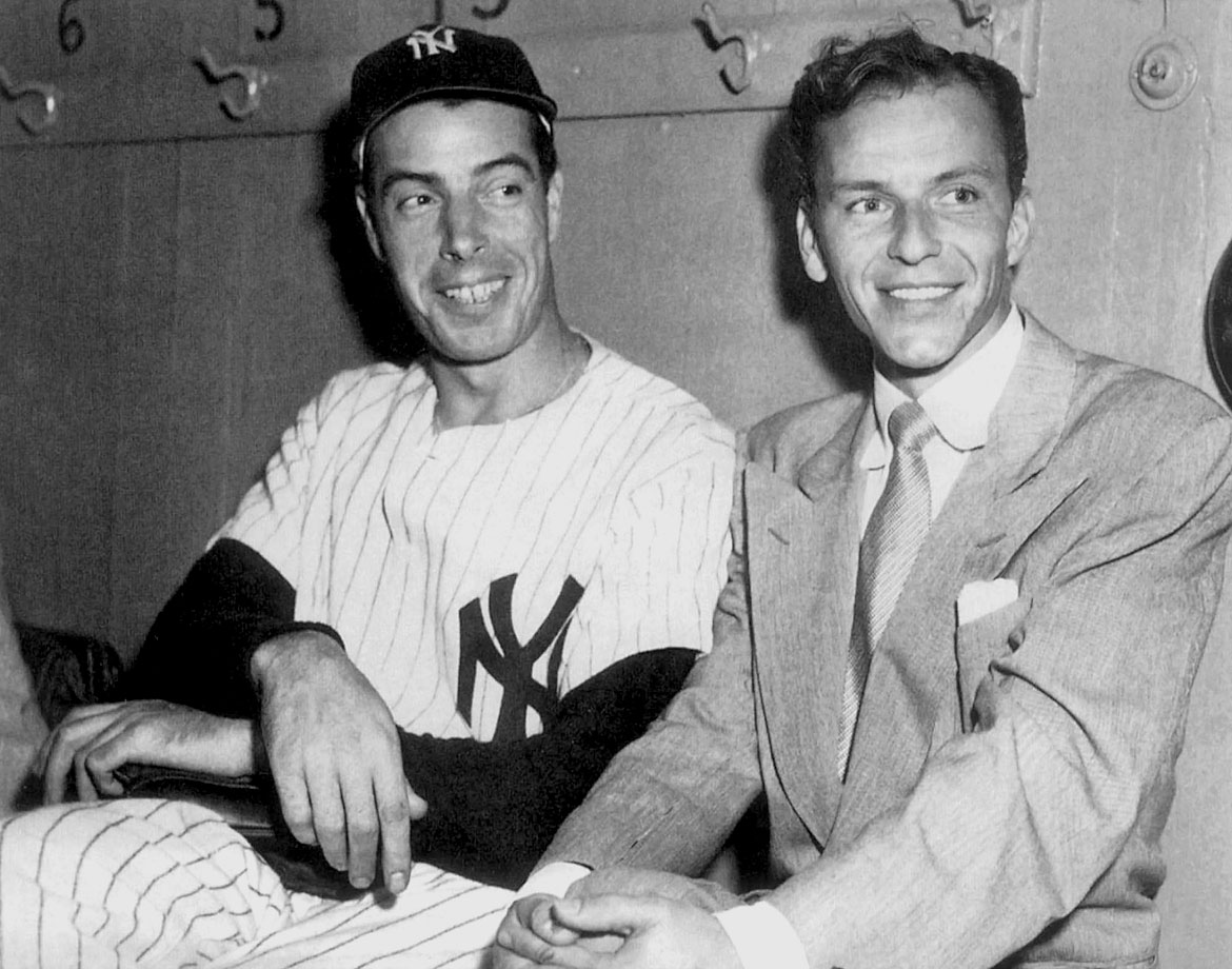 Joe DiMaggio sits with Frank Sinatra in the dugout at Yankee Stadium in 1949.