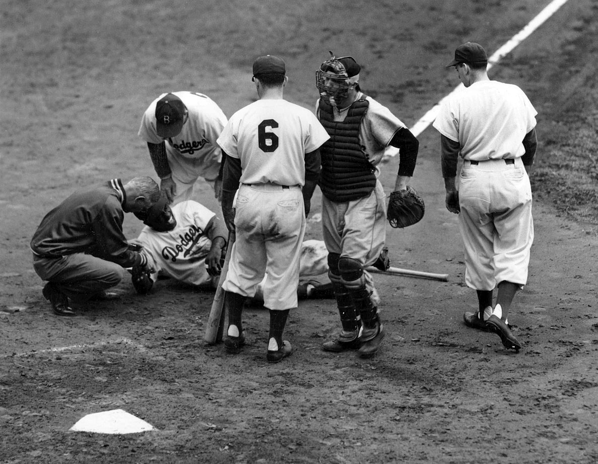 Jackie Robinson is helped by the Dodgers trainer and third base coach after being struck in the head by a pitch during a game in the 1949 season in Brooklyn.