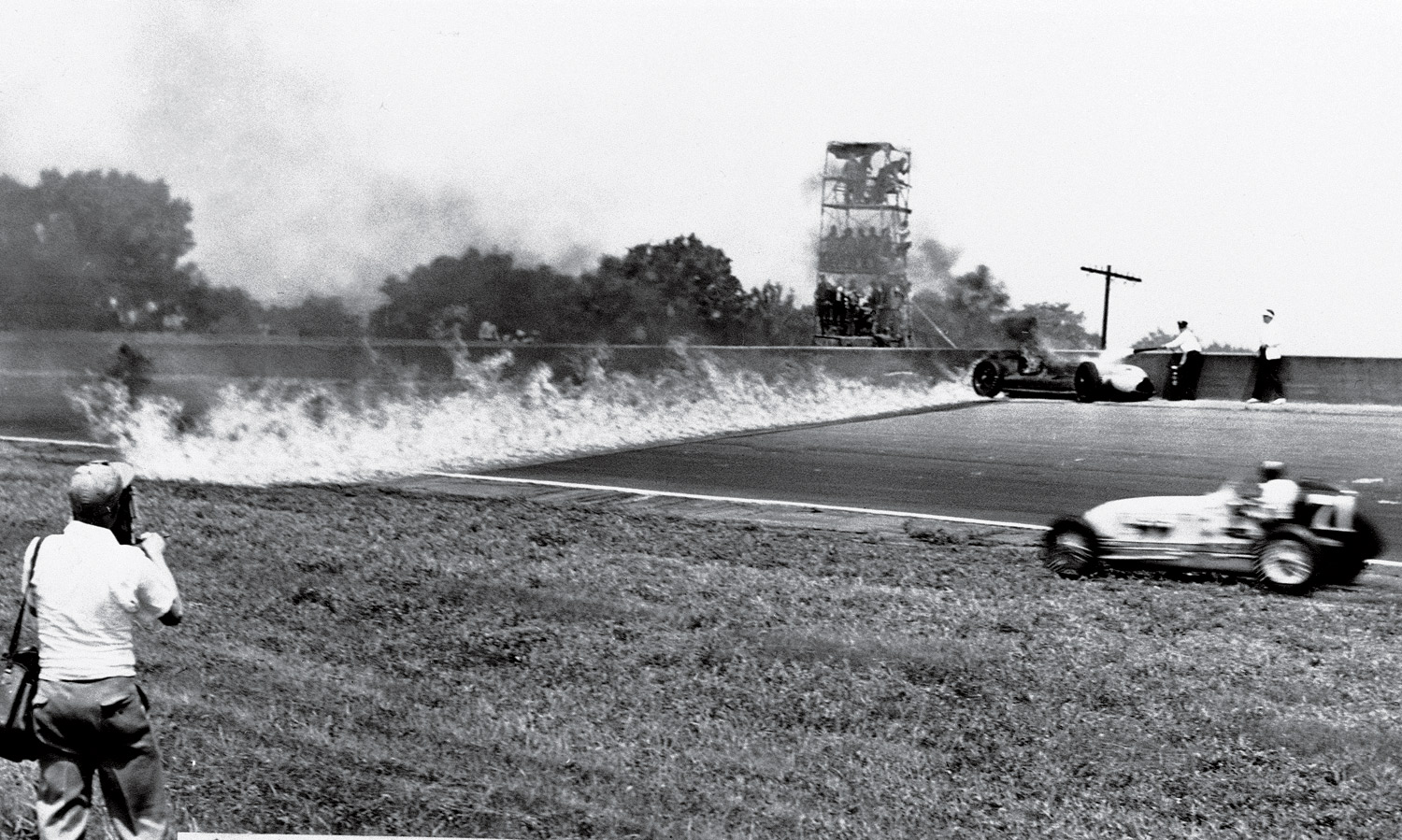 Norm Houser took an infield detour to dodge the trail of fire left by Duke Nalon's crash into the retaining wall. Nalon's injuries knocked him out of racing for two years.