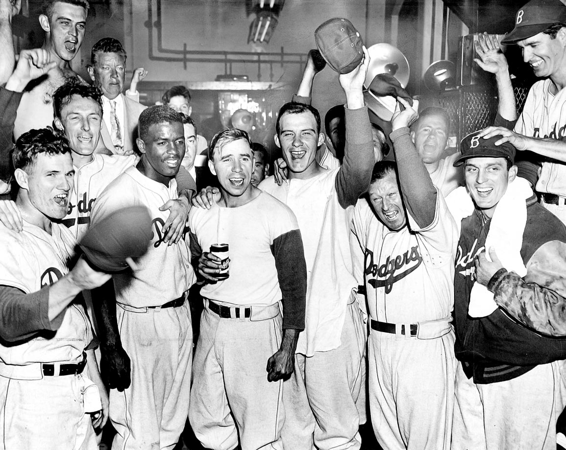 The Dodgers, including (from left) Wayne Terwilliger, Jackie Robinson, Pee Wee Reese, Preacher Roe, Chuck Dressen and Carl Erskine, celebrate in the clubhouse after defeating the Phillies in 14 innings to tie the Giants for first place in the National League on Sept 30, 1951.