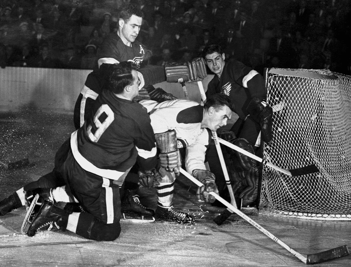 It didn't always take three Hall of Famers to stop Rocket Richard, but with the Stanley Cup on the line, the Red Wings weren't taking any chances. Red Kelly (top left) and Gordie Howe (bottom) sandwiched Montreal's dangerous Rocket in this Game 1 image. Goalie Terry Sawchuk blanked Richard in all four games of Detroit's sweep.