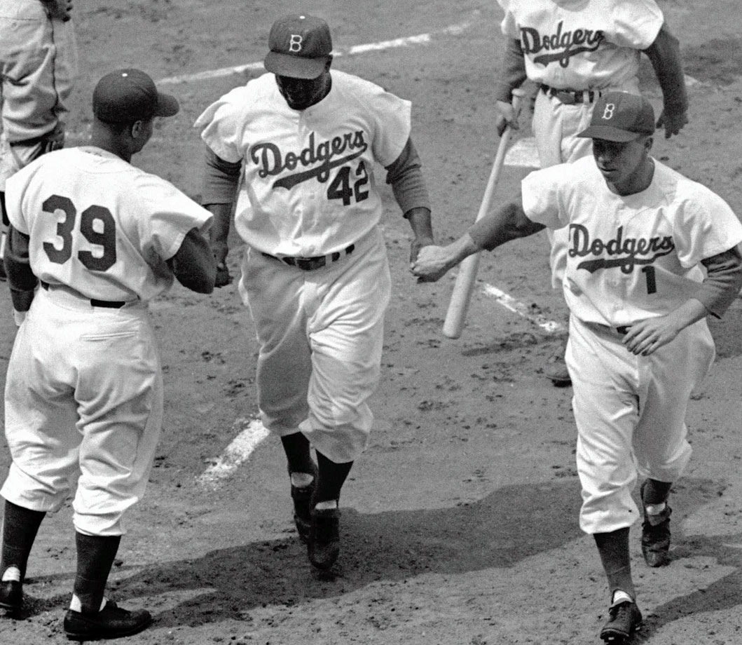 Roy Campanella and Pee Wee Reese welcome Jackie Robinson at home plate after his first inning two-run homer against the Pirates at Ebbets Field on April 15, 1954.