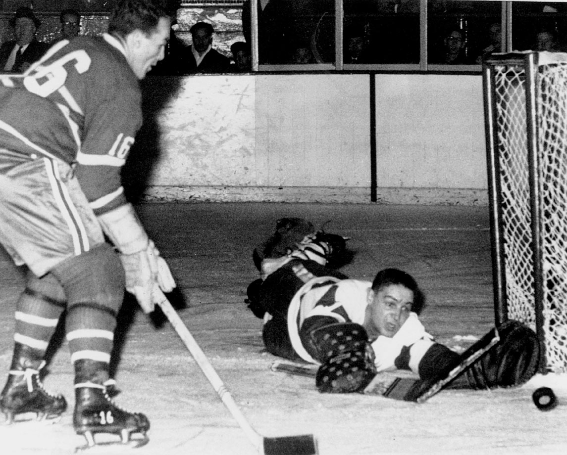 "Diminutive winger Tony ""Mighty Mouse"" Leswick (inset) ended a defensive struggle with a goal at 4:29 of OT to give Detroit the Cup. Goalies Terry Sawchuk (Detroit) and Gerry McNeil (Montreal) seemed locked in until Leswick floated a shot that glanced off Canadiens defenseman Doug Harvey's glove and into the net. The match remains the last Game 7 to decide the championship in OT."