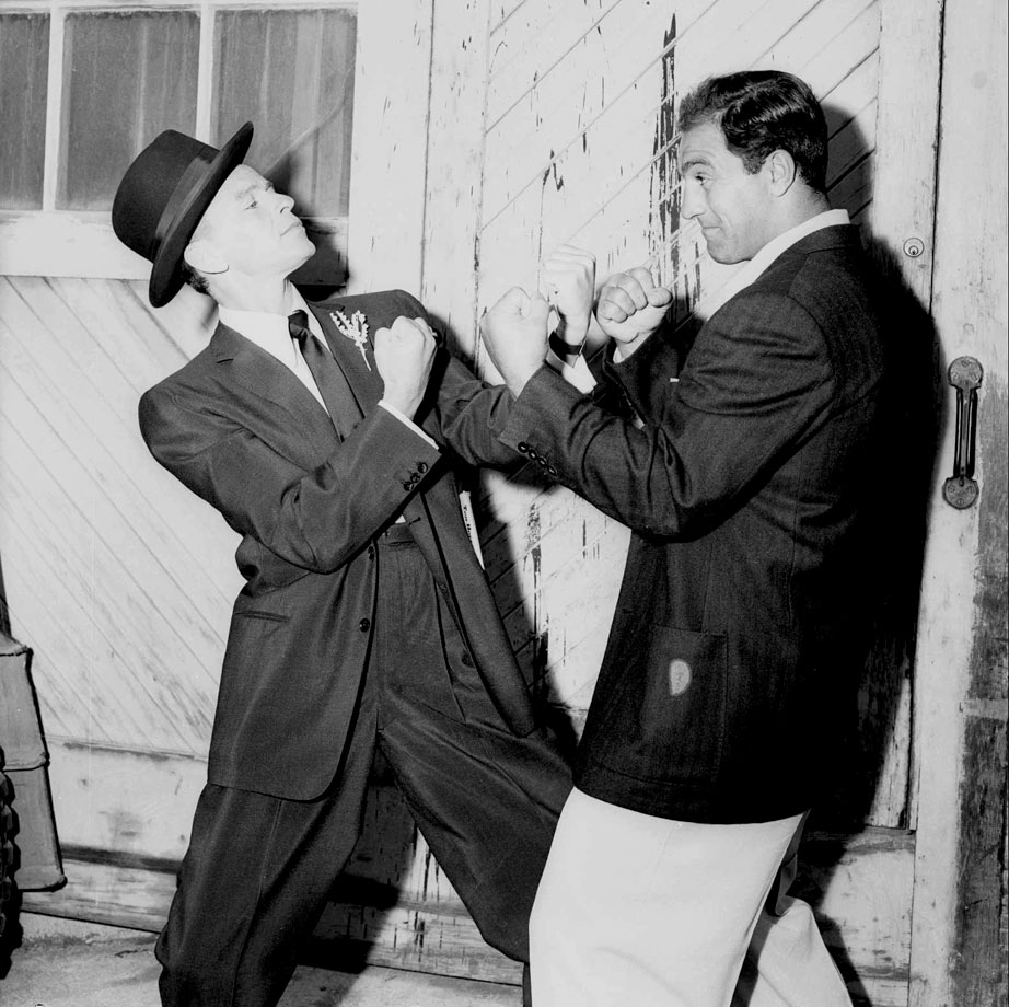 "Frank Sinatra, who fancies himself something of a pugilist, squares off with world heavyweight champion Rocky Marciano. The horseplay occurred while Marciano visited the ""Guys and Dolls"" movie set in Hollywood on May 26, 1955."