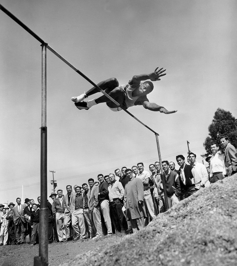 While at the University of San Francisco, Bill Russell also competed in track and field. Shown here in the high jump, and missing one shoe, Russell was attempting to clear 6-9 1/4. He tied for third at this meet in Los Angeles by clearing 6-6 1/4.