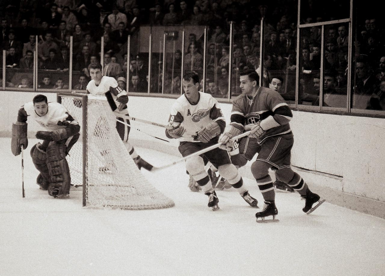 "Gordie Howe and the Detroit Red Wings battle the Montreal Canadiens. He scored 33 goals and 77 points in 64 games that season and won the Hart Memorial Trophy as the NHL's MVP, his fourth of six such honors. His rugged style of play was summed up by the expression ""Gordie Howe hat trick""—when a player has a goal, an assist and a fight in the same game."