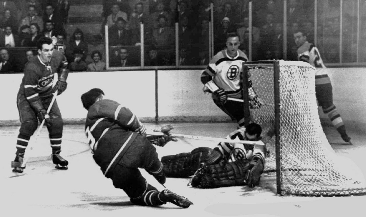 """The glove of Bruins goalie Don Simmons swallowed this shot by Maurice """"Rocket"""" Richard in Game 5, but it was one of the few pieces of puck he grabbed that night. Montreal took the game 5-1, clinching the series. Richard tallied eight goals in 10 playoff games that spring to finish second in the scoring race behind teammate Bernie Geoffrion (11)."""