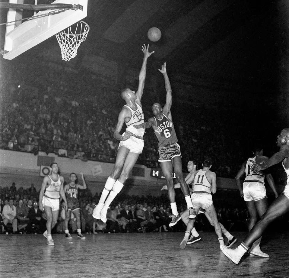 Bill Russell shoots over the reach of Philadelphia Warriors center Wilt Chamberlain during a game at Convention Hall in Philadelphia.