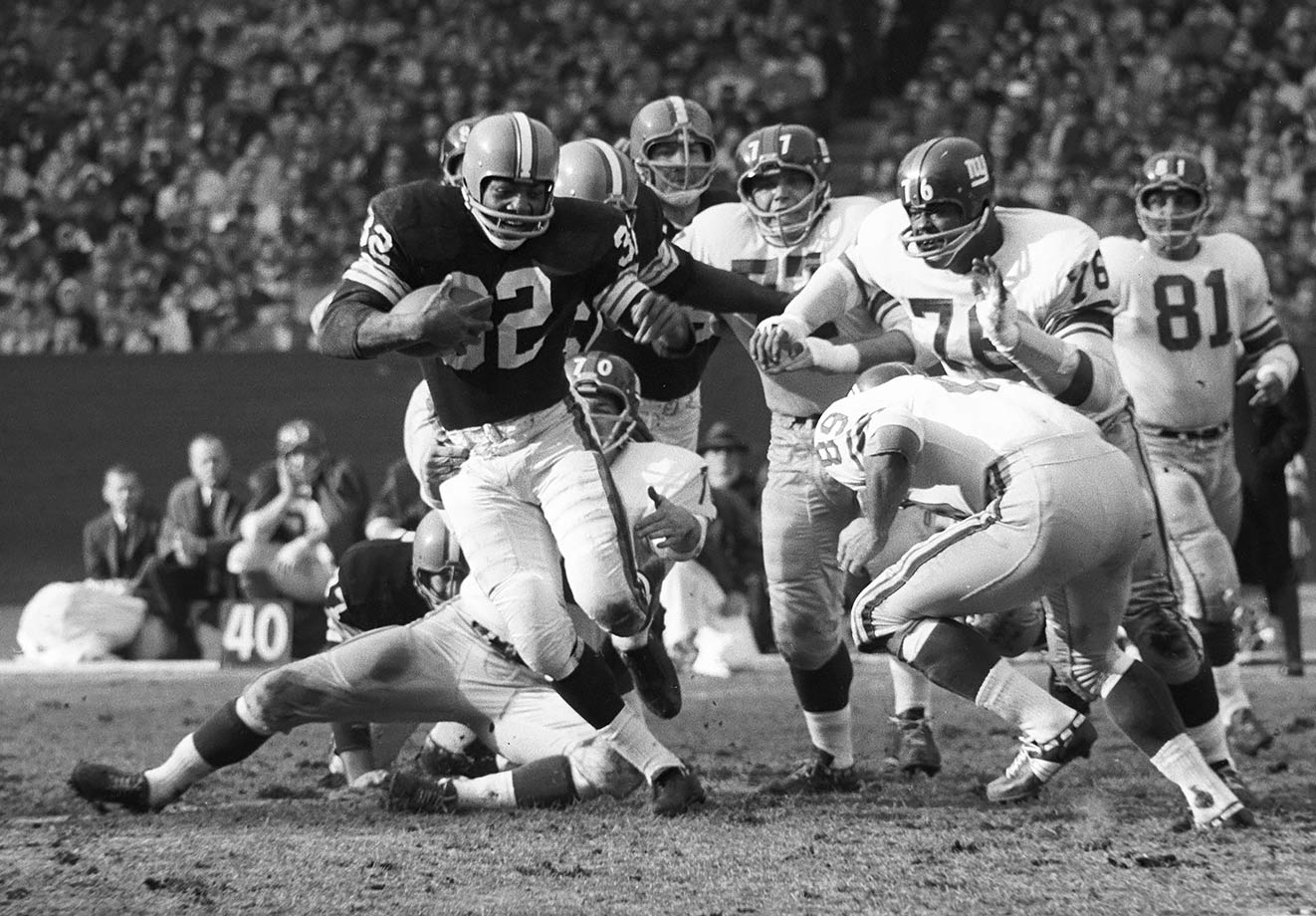 Jim Brown extends a stiff arm as he runs away from the New York Giants defense at Cleveland Municipal Stadium in 1961. Brown did a lot of running away from defenses in 1961 as he topped 100 yards per game for the fourth straight season, racking up 1,408 rushing yards plus another 459 receiving.