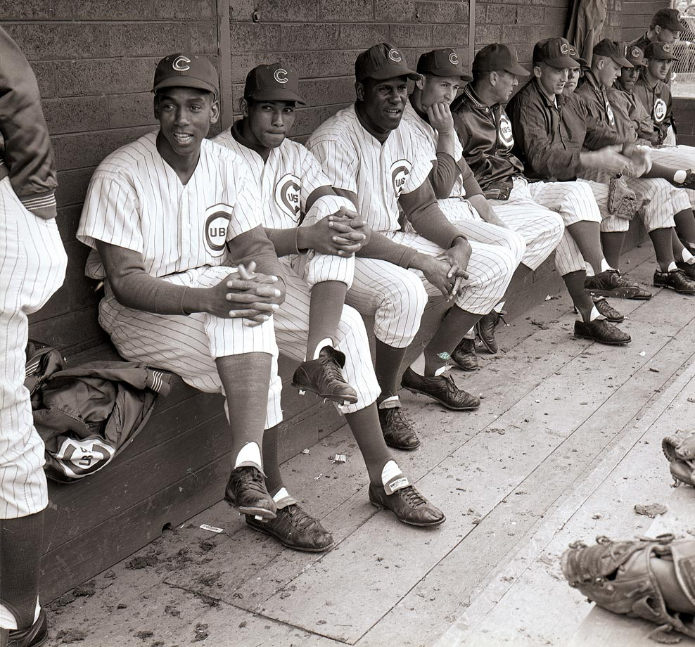 Ernie Banks sits with Billy Williams, George Altman and Ron Santo in the dugout.