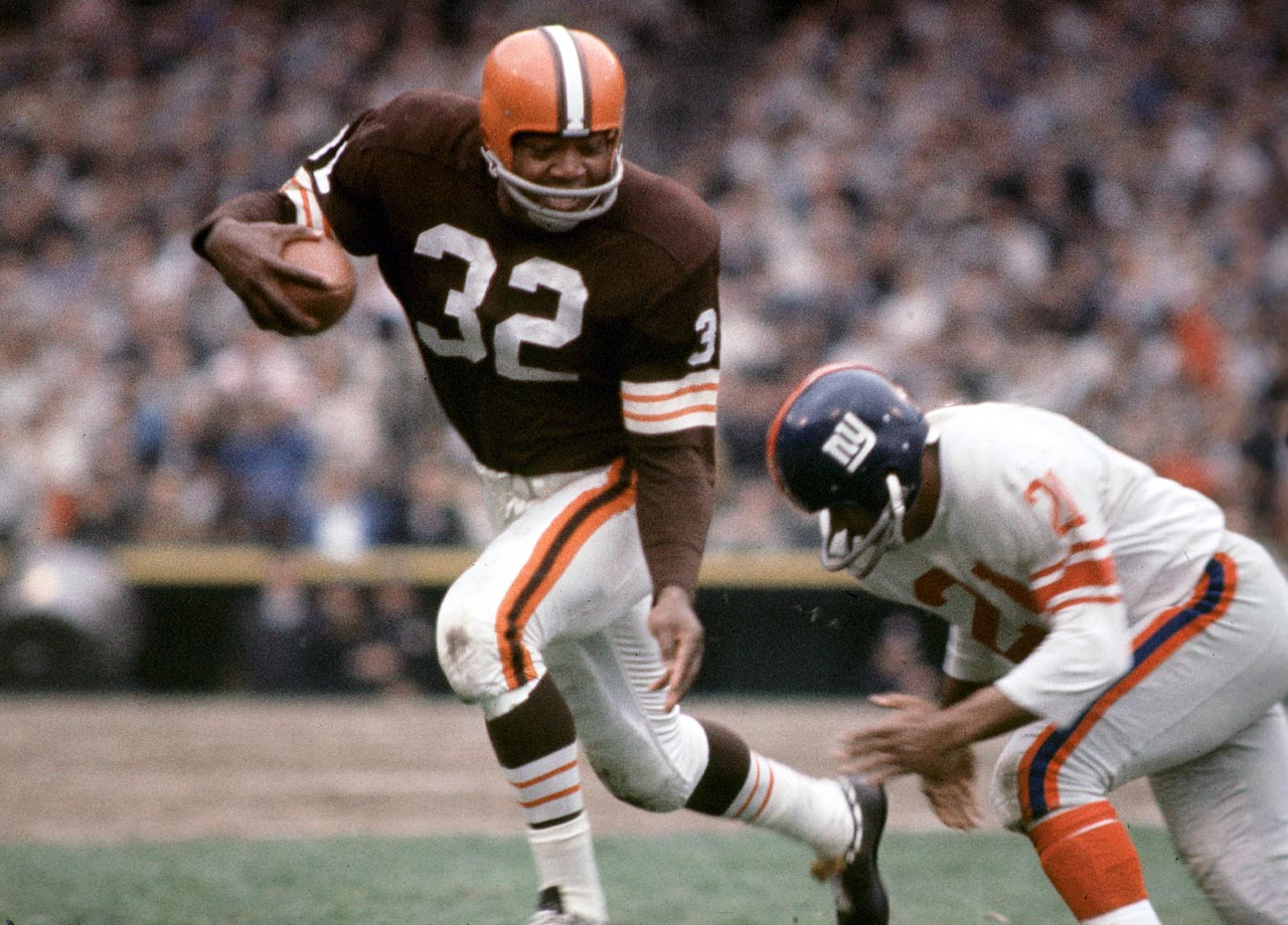 Jim Brown rushes agains the New York Giants during a game in 1963. Brown's career average of 104.3 yards per game is still the best in NFL history.